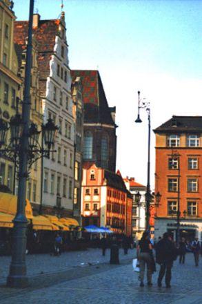 """Vi befinner oss på Rynek (""""Torget""""). Här ser vi den västra sidan av torget, kallad """"Ullmarknaden"""". Sydsidan kallas """"Fiskmarknaden"""" och norrsidan """"Sötsaksmarknaden"""". I bakgrunden skymtar Elisabetkyrkan."""